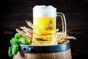bicchiere di birra su barile con grano e luppolo